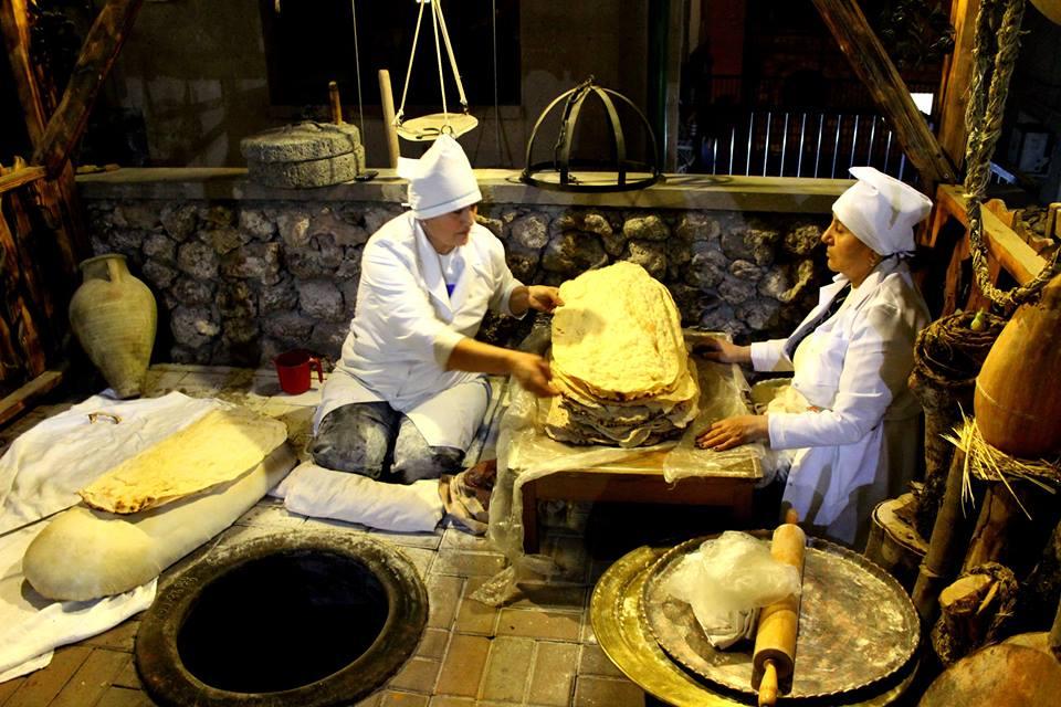 Женщины пекут лаваш в тандыре